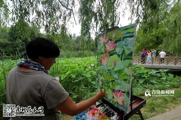 图为写生爱好者在湖边进行荷花作品创作(图片来源:青岛新闻网)